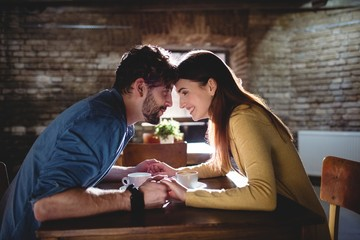 Side view of couple holding hands at cafe