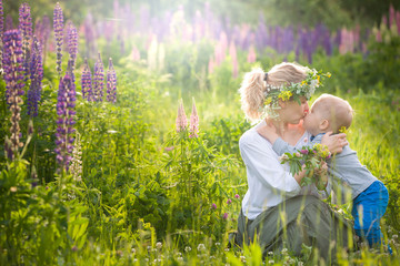 Beautiful young woman hugging and kissing her adorable little toddler boy on a sunny flower meadow. Happy family enjoying sun in the park on s summer day. Mother with child on sunset. outdoors.