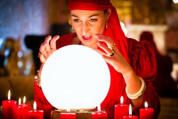 Wahrsagerin oder esoterisches Orakel sieht während einer Seance in die Zukunft durch einen Blick in ihre Kristallkugel um diese zu deuten und Fragen zu beantworten