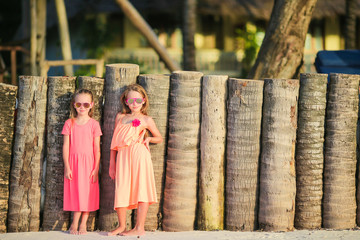 Adorable little girls on white beach. Happy sisters