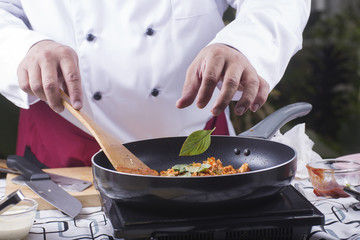 Chef putting basil to pan for cooking spaghetti chicken sauce