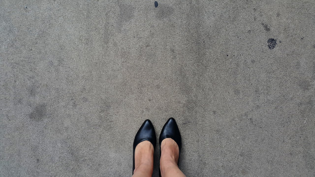 Black high heels on cement floor with copy space