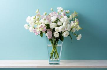 青い背景と白い薔薇とピンクのデンファレと花瓶