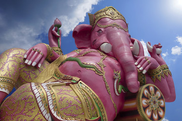 Pink Ganesha statue,the elephant-headed god in Hinduism,the elephant deity riding a mouse,Lord of Success,prime Hindu deities, Blue sky and cloud, sunlight effect on the right side of picture