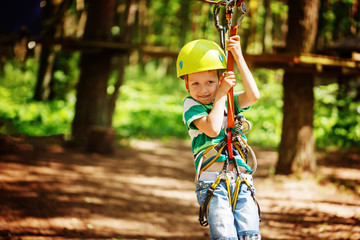 Adventure climbing high wire park - little child on course in mountain helmet and safety equipment