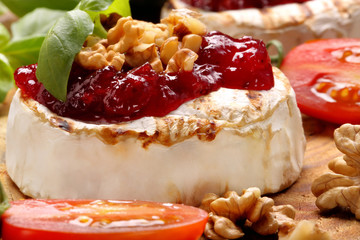 Grilled brie cheese with cranberry jam and walnuts on old wooden