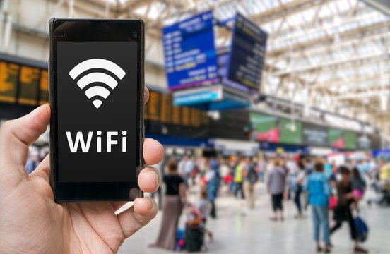 Man holds smartphone with free wifi in train station.