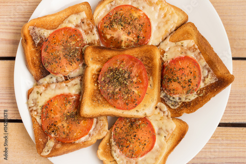 Foto: toast with cheese tomato basil oregano on a wooden background