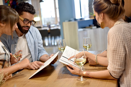 Young trendy people in restaurant looking at menu