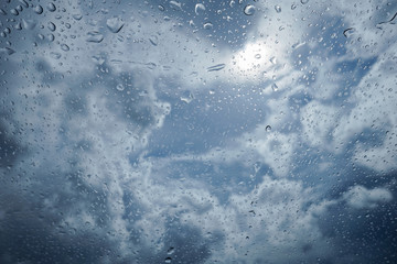 water drop of rain on a glass, blurred blue sky and cloud in background, selective focus