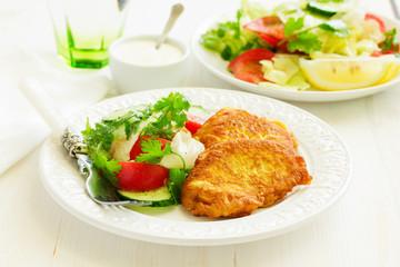 Pork chop in batter with vegetable salad.