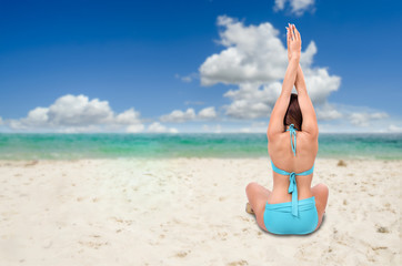 woman on tropical resort beach doing yoga relaxing