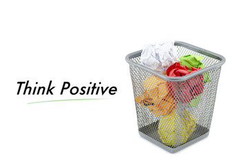 "conceptual image with word ""THINK POSITIVE"" over crumple paper in metal dustbin and isolated white background"