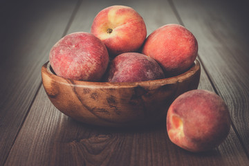 wooden bowl with some peaches on brown table