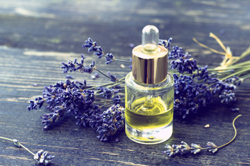 Bottle of lavender oil and lavender flowers on wooden background  - vintage stylized photo