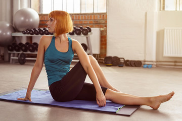 frau dehnt den rücken im fitness-studio