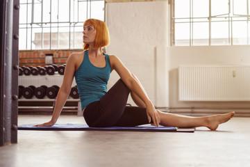 frau dehnt den rücken im fitnessstudio