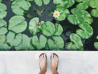 Selfie of feet in sandals shoes on pavement with lotus flower po
