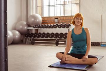 attraktive frau sitzt auf einer matte im fitness-studio