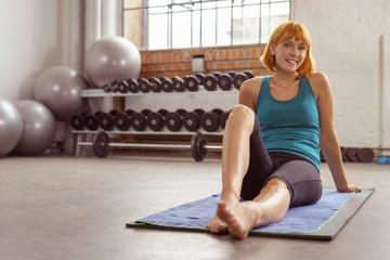 glückliche frau sitzt auf einer matte im fitness-studio