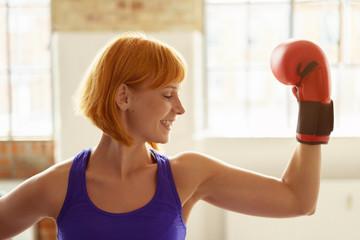 lachende frau mit boxhandschuhen spannt ihre armmuskeln an