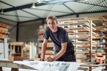 Portrait of young male carpenter at workbench