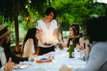 Group of friends having meal outdoors, woman bringing birthday cake to friend