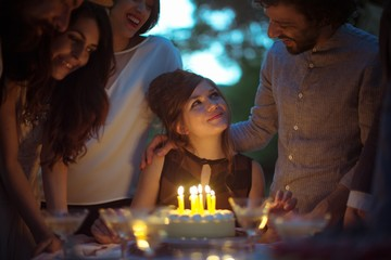 Teenage girl celebrating her birthday party with friends at night