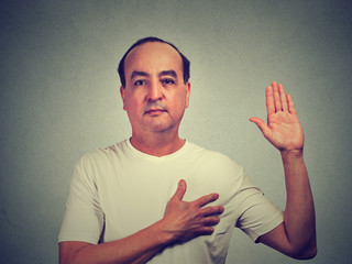 Middle aged man making a promise isolated on gray wall background