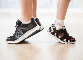 Child's and woman's legs in sports shoes