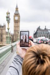 Woamn taking a photo to big ben