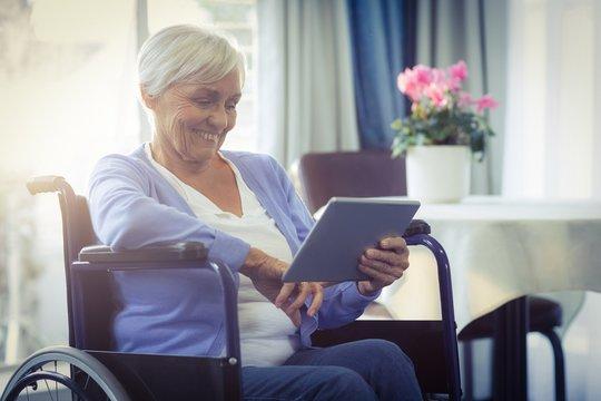 Happy senior woman on wheelchair using digital tablet