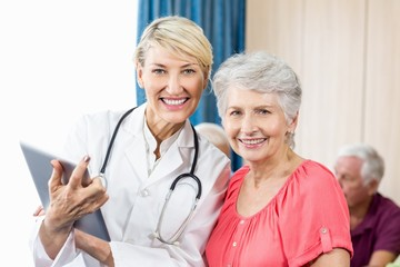 Smiling senior woman and nurse holding a tablet