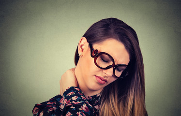 tired woman with glasses massaging her painful neck