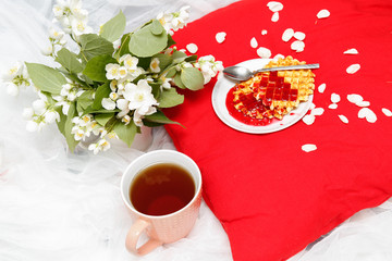 Breakfast in bed -tea and biscuits with strawberry jam