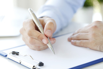 Fill the form. Close-up image of a businessman's hands initialing some paperwork.
