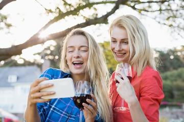 Happy beautiful women looking at mobile phone