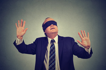 business man in suit blindfolded stretching his arms out. vision