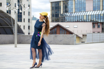 Young beautiful woman in a blue dress walking on the summer stre