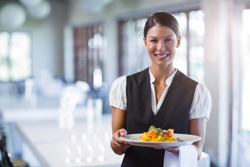 Waitress holding plate of meal in a restaurant