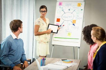Woman discussing flowchart on white board with coworkers
