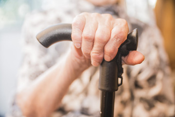wrinkled hands of an old woman pensioner grandmothers on the cane stick