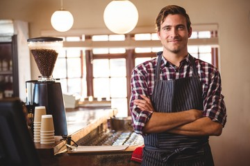 Portrait of smiling waiter standing with arms crossed