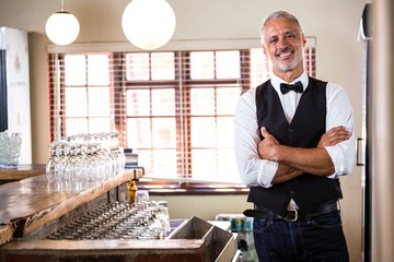 Portrait of smiling bartender standing with arms crossed