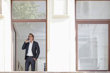Businessman telephoning with smartphone while looking through open window