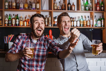 Young people with beer watching football in a bar