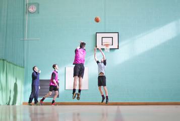 Gym teacher teaching high school students playing basketball in gym class
