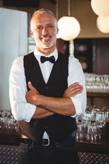 Portrait of bartender standing with arms crossed