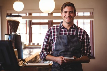 Portrait of bartender standing with notepad