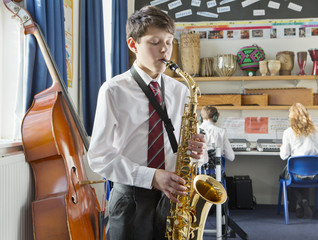 Middle school student playing saxophone in music classroom